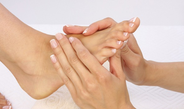 woman massaging patient's foot