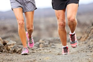Runners running shoes on trail run. Ultra running athletes legs